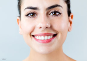 Female With Pink Lips and Thick Black Eyebrows Smiling