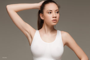 Female in White Tank Holding Ponytail With Right Hand