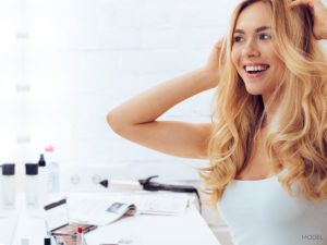 Blond In White Tank Sitting at Home Lifting Hair With Hands