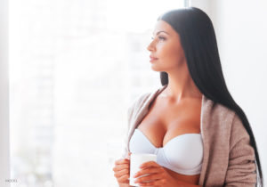 Female With Black Hair In White Bra And Sweater Holding White Mug Looking Out Window