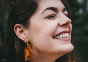 Female With Dark Hair and Orange Earrings Smiling From Excitement
