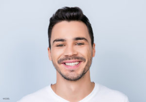 Young Caucasian Male With Clean Face In White T-shirt On Light Blue Background