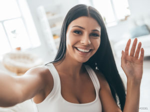Confident and Happy Female With Black Hair and White Tank Taking Selfie Inside Home