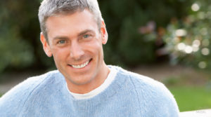 Mature Caucasian Male With Blue Sweater Smiling Outdoors