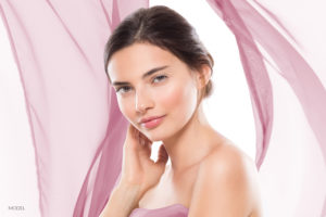 Woman Showing Off Beautiful Face With Pink Chiffon Material In Background