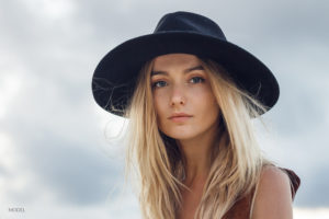Blond Female Wearing Black Hat and Blouse Outside With Clouds In Sky