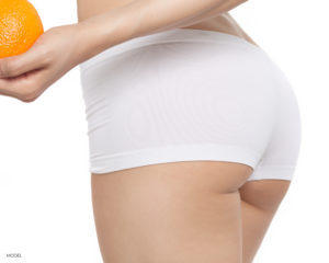 Female Buttocks In White Boy Shorts Showing Holding An Orange With Hand