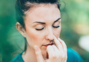 Female Pressing Finger On Left Nostril Breathing Deeply Outdoors